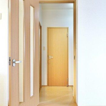 キッチン右のドアから玄関へ。正面がトイレ、左が脱衣所。(※写真は1階の同間取り別部屋のものです)