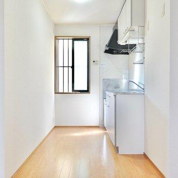 DKの奥には窓のある明るいキッチン。(※写真は1階の同間取り別部屋のものです)