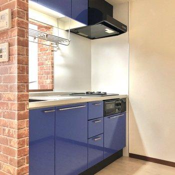 【LDK】レンガ調の壁、青い収納が印象的なキッチン。