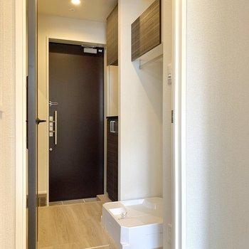 扉を開けると洗濯機置き場。棚が上にあり便利です。※写真は前回募集時のものです