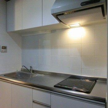 2口IHタイプのキッチンは広さもあり機能的ですね(※写真は8階同間取り別部屋のものです) (※一部、壁の色が異なります)