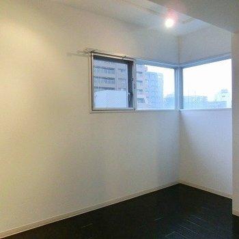 コーナー窓にレールライトのある6帖の洋室(※写真は8階同間取り別部屋のものです) (※一部、壁の色が異なります)