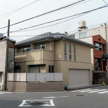 交差点の角に立つ、戸建てのような外観のアパート。