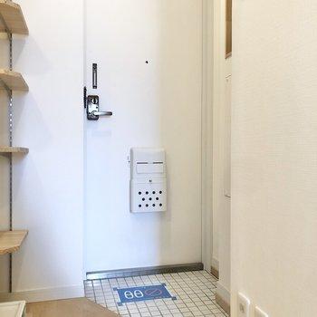玄関土間は小さめ。清潔感のある白いタイルです。