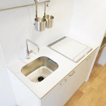 シンプルにまとまったキッチン。IHの上でまな板も使えます。※写真は同間取り別部屋です
