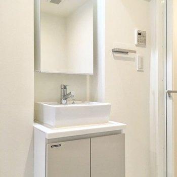 向かいには洗面台。鏡の裏は収納になっています。