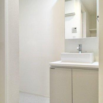 洗面台はスタンダードなタイプ。鏡の裏側は収納になっています。