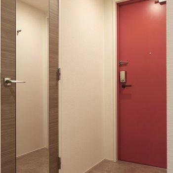 赤いドアが印象的な玄関です(※写真は12階の同間取り別部屋、モデルルームのものです)