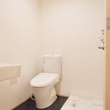 お手洗いと洗濯機置場。ブラックの床材が映える空間です。