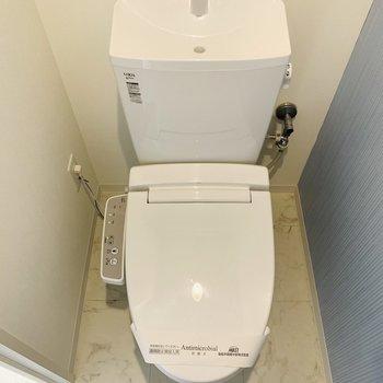 ウォシュレット付きのトイレ。クロスも爽やか。(※写真は7階の反転間取り別部屋のものです)