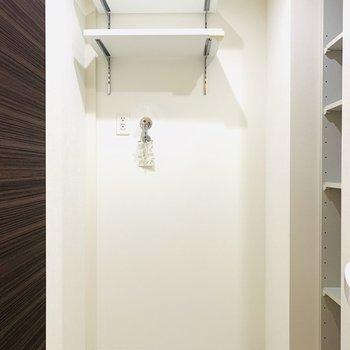 左手には洗濯機置き場。上部には収納棚も。(※写真は7階の反転間取り別部屋のものです)