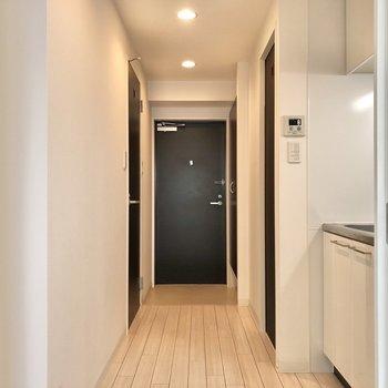 廊下へ。左側に脱衣所。右側にキッチンです。(※写真は11階の同間取り別部屋のものです)