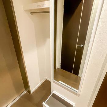 玄関にはコート掛けと姿見付き。さらに姿見の下には折りたたみ式の腰掛けまで!
