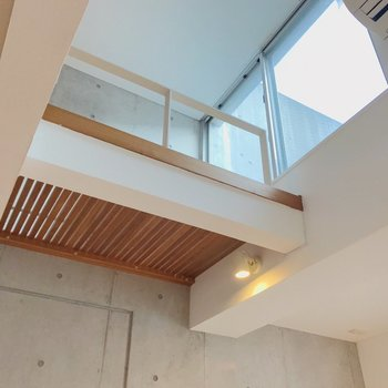 見上げるとコンクリの壁とルーバー状のロフトの床。かっこいい……(※写真は別棟の同間取り別部屋のものです)