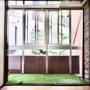 大きな窓に囲まれた人工芝。 外にいるかのようです。