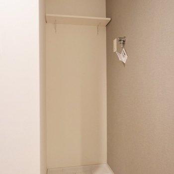 洗濯機置場は玄関横にあります。突っ張り棒と布で隠すことも可能。