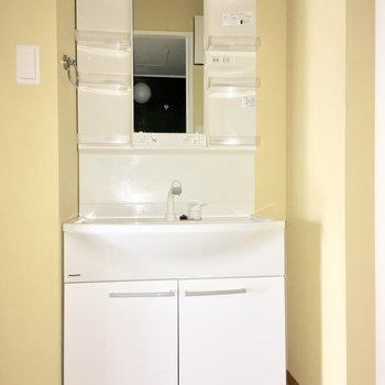 レモンイエローのサニタリー。ラックが多くて洗面台も使いやすそう。※写真は4階の同間取り別部屋のものです