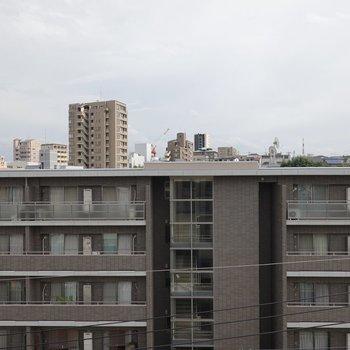 正面には同じほどの高さのマンション。空が抜けているので気持ち良い。