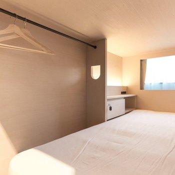 区画内には幅90cmのベッドとサイドボードにハンガーラックがあります。