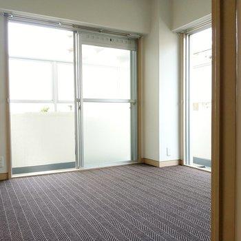 キッチン横の4.6帖の洋室。床はシックなカーペット。