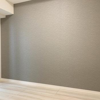 グレーの壁沿いにベッドを。※写真は6階の反転間取り別部屋のものです