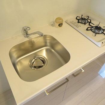 キッチンは2口コンロのシステムキッチンです。(※写真は9階の反転間取り別部屋のものです)