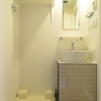 シンプルな洗面台と、隣にある洗濯機置き場(※写真は9階の反転間取り別部屋のものです)