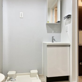 脱衣所。シャープな印象の洗面台と洗濯機置き場。