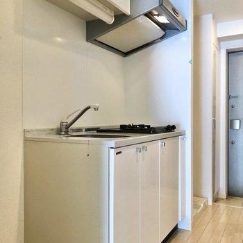 白いキッチンには上下収納付き。