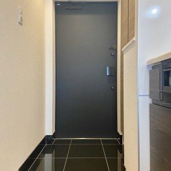 玄関は黒のタイル、ツルッとした質感がお気に入り。横の小さな棚には鍵などを置けますよ。