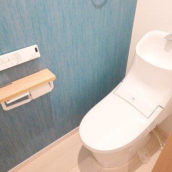 スタイリッシュなウォシュレット付きトイレ◎アクセントクロスも独特で素敵。上部には収納棚も付いています。
