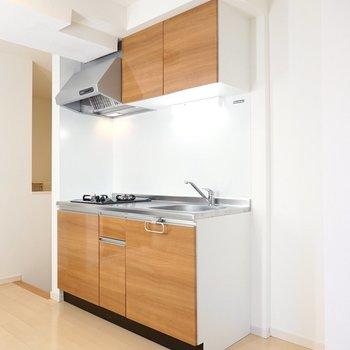 ドレッサーの正面には明るい木目調のキッチン。冷蔵庫置場は右側に。