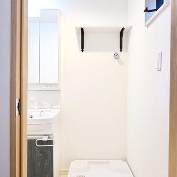 入って正面には洗濯機置場。洗剤が置ける棚付き!
