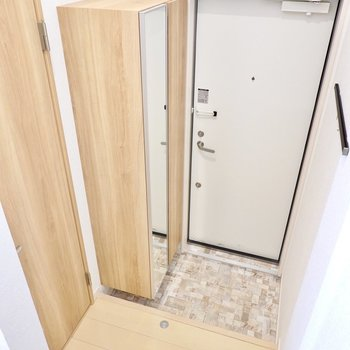 降りた先が玄関。姿見付きの靴箱があります。左のドアの先はトイレ。