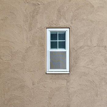 脱衣所への階段の窓からはお隣さんの壁。塗り壁と小窓が素敵ですね。