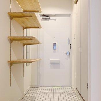 玄関には白タイル&可動式の棚を設置。