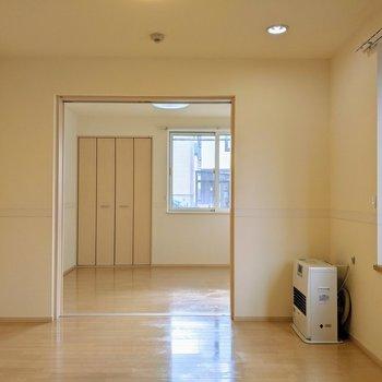 【リビング】扉を開くと洋室窓から日差しが差し込みます。