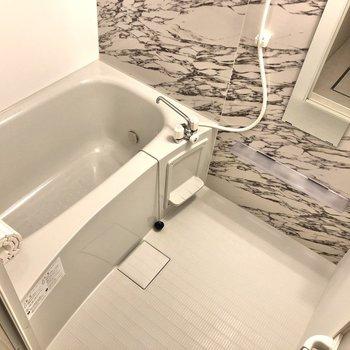 大理石調の壁材が印象的な浴室。