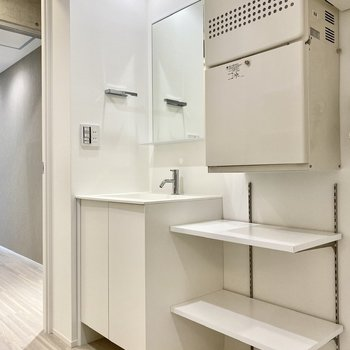 シンプルかつスタイリッシュな洗面台。サイドのラックにタオルなど置いておけますね。