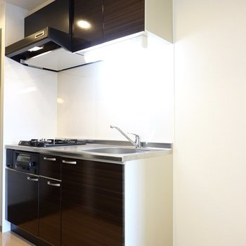白い空間に黒いキッチンパネルが映えます。冷蔵庫置場は右側に。