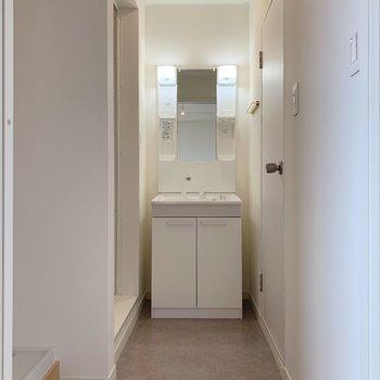 水回り、いってみよー!グレーの床、奥に見えるのはまだまだ綺麗な洗面台。(※写真は前回施工した反転間取り別部屋のものです)