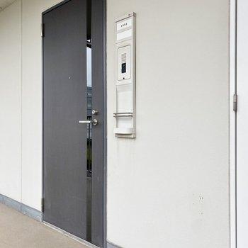 玄関前共用部。スリットの入ったドアがお洒落。