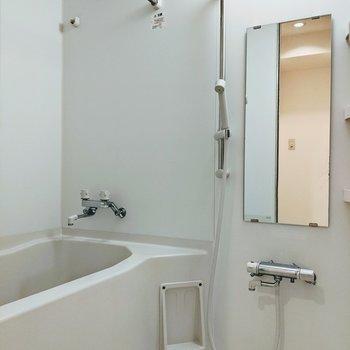 浴室に縦長の大き目の鏡、洗濯物干しがついています。