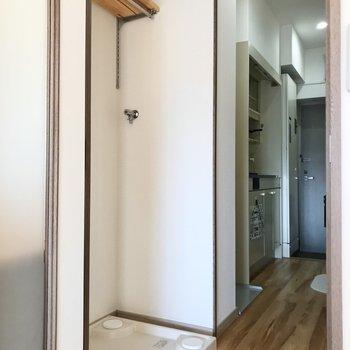 まず洋室側に洗濯機置き場。上の棚が便利◯(※写真の小物は見本です)