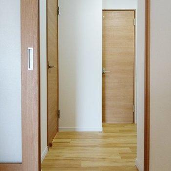 キッチン後ろから廊下へ。正面がトイレ。左が洋室です。