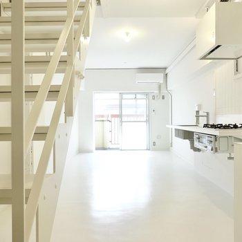 玄関を抜けると、スケルトン階段の向こうにダイニングキッチンが広がります。