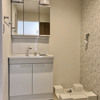 丸いタイルクロスの脱衣所。スタイリッシュな洗面台と洗濯機置き場も。