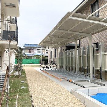 自転車置場は一台ずつラック付。奥には駐車場も。