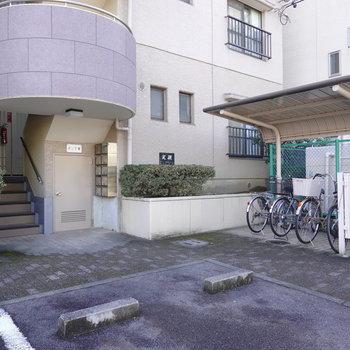 コンパクトな屋根付き駐輪場がある方がお部屋の階段への入り口。