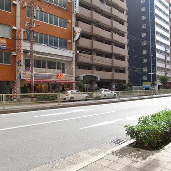 【周辺環境】マンション前の大通り。道路沿いにマンションとお店が並んでいます。